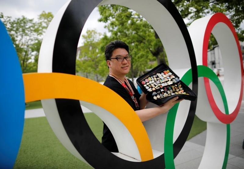 Yoshiyuki Terajima, a pin collector based in Tokyo, shows his collection next to the Olympic rings monument in Tokyo