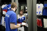 Russian athlete Musa Mogushkov, center, tries on the new Olympic gear for Russian athletes for the Tokyo Games by the brand ZASPORT in Moscow, Russia, Thursday, July 1, 2021. (AP Photo/Alexander Zemlianichenko)