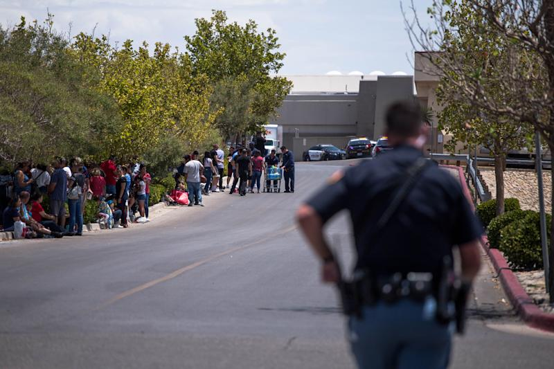 Individuals that were evacuated sit in a parking lot across from a Walmart where a shooting occurred at Cielo Vista Mall in El Paso, Texas, Saturday, Aug. 3, 2019. | JOEL ANGEL JUAREZ—AFP/Getty Images
