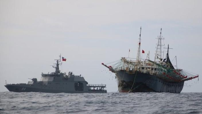"""One vessel, part of a fleet of hundreds of Chinese fishing boats, sails next to a Chilean Navy ship in Pacific Ocean international waters near Chile""""s exclusive economic maritime zone, off the coast of Arica and Parinacota November 30, 2020."""