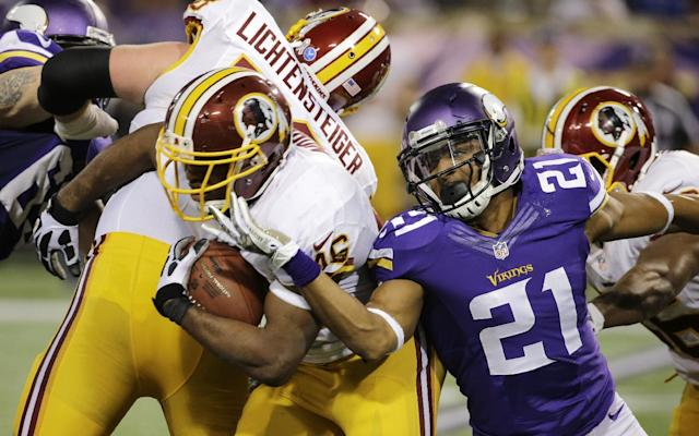 Washington Redskins running back Alfred Morris, left, tries to break a tackle by Minnesota Vikings cornerback Josh Robinson, right, during the second half of an NFL football game, Thursday, Nov. 7, 2013, in Minneapolis. (AP Photo/Ann Heisenfelt)