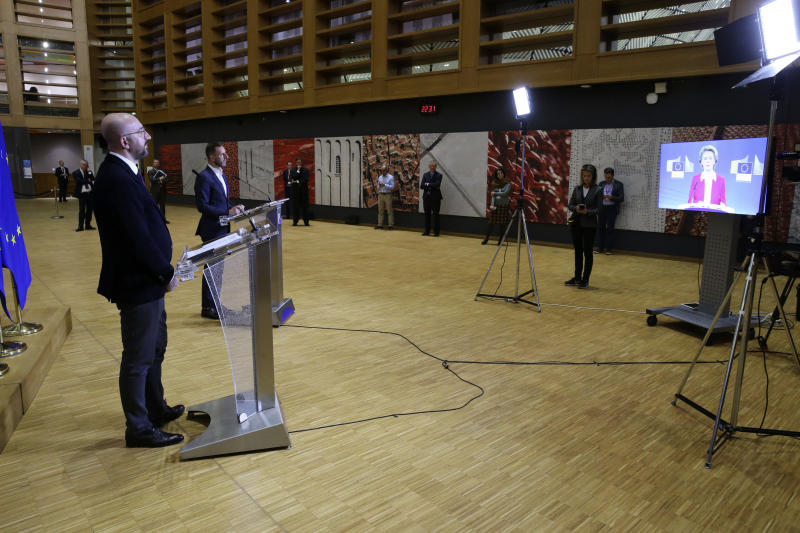 European Council President Charles Michel, left, speaks during a joint media conference with European Commission President Ursula von der Leyen, on screen right, after an EU summit by video conference in Brussels, Thursday, March 26, 2020. Following the informal video conference, members of the European Council adopted a statement on the EU actions in response to the COVID-19 outbreak. The new coronavirus causes mild or moderate symptoms for most people, but for some, especially older adults and people with existing health problems, it can cause more severe illness or death. (Francois Walschaerts, Pool Photo via AP)