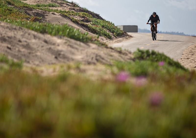 A man rides a bike at Dockweiler State Beach on March 15.