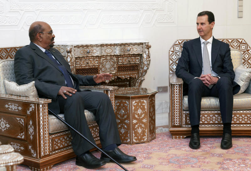In this photo released by the Syrian official news agency SANA, Syrian President Bashar Assad, right, meets with Sudan's President Omar al-Bashir in Damascus, Syria, Sunday, Dec. 16, 2018. Sudan's president has become the first Arab League leader to visit Syria since a war erupted there nearly eight years ago. (SANA via AP)