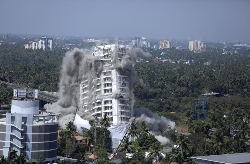 High-rise luxury apartment apartment Holy Faith H2O is brought to the ground by controlled implosion in Kochi, India, Saturday, Jan. 11. 2020. Authorities in southern Kerala state on Saturday razed down two high-rise luxury apartments using controlled implosion in one of the largest demolition drives in India involving residential complexes for violating environmental norms. (AP Photo/Prakash Elamakkara)