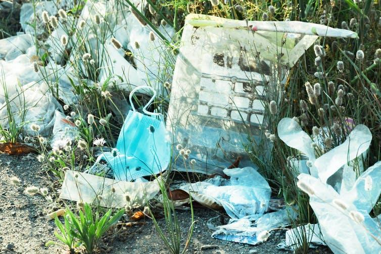 Discarded plastic waste in a grassy area, including plastic gloves and face masks.