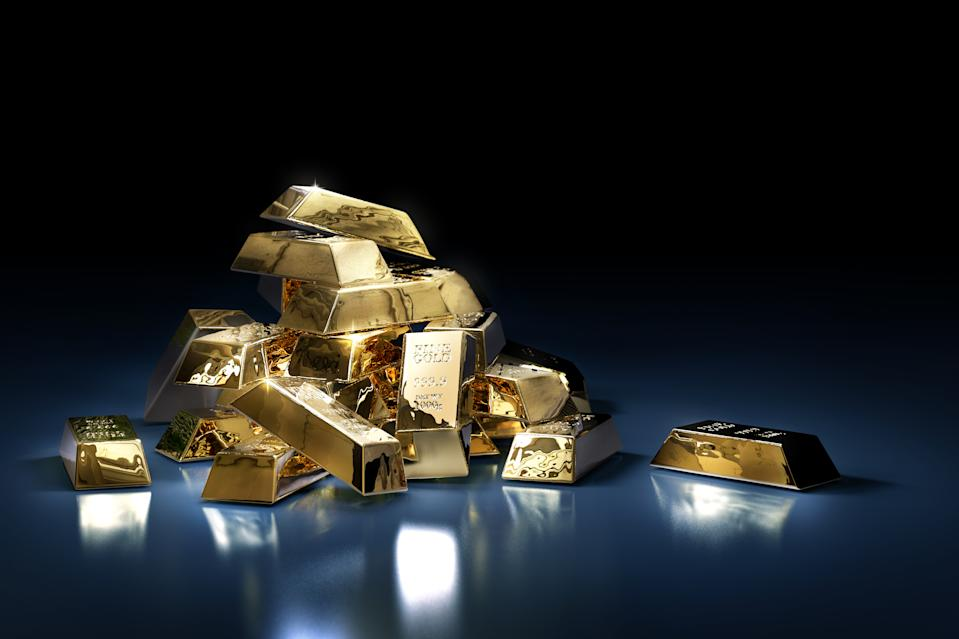 A pile of gold bars or ingots on a dark background. Photo: Getty Images
