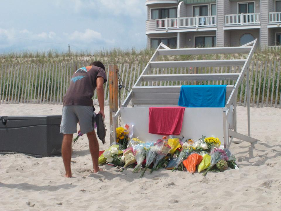 Michael Cordiano, a lifeguard in Berkeley Township, lays flowers on Tuesday at the base of a lifeguard stand.