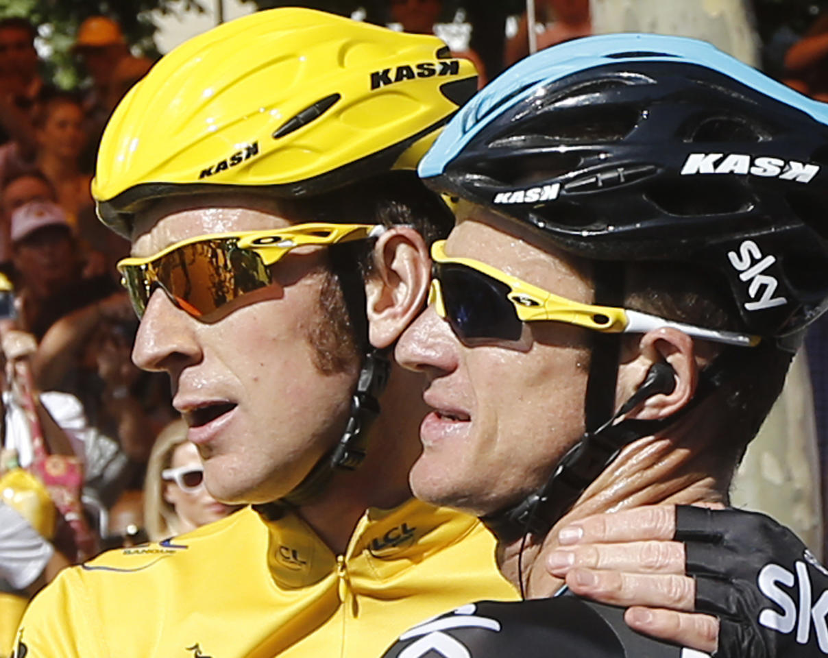 Bradley Wiggins, winner of the 2012 Tour de France cycling race, left, hugs teammate Michael Rogers of Australia, after the last stage of the the Tour de France cycling race over 120 kilometers (74.6 miles) with start in Rambouillet and finish in Paris, France, Sunday July 22, 2012. (AP Photo/Laurent Cipriani)