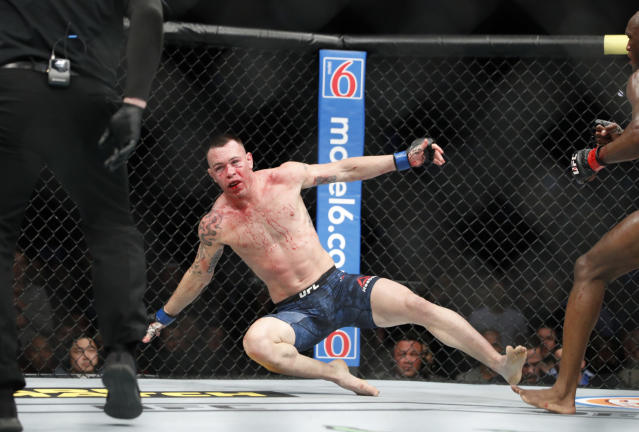 Kamaru Usman knocks Colby Covington to the mat in a mixed martial arts welterweight championship bout at UFC 245, Saturday, Dec. 14, 2019, in Las Vegas. (AP Photo/John Locher)
