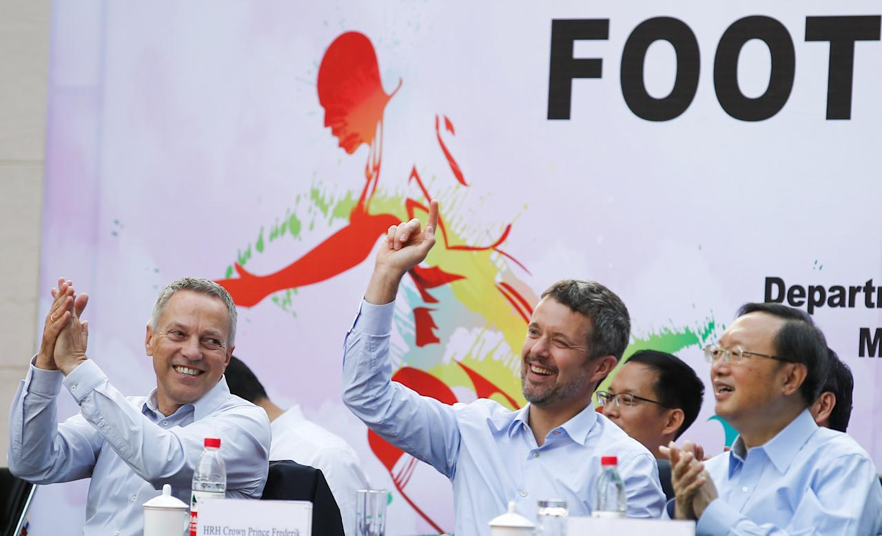 Danish Crown Prince Frederik (C) and Danish ambassador Carsten Damsgaard (L) celebrate a Danish goal as Chinese State Councillor Yang Jiechi (R) applauds during the final of the Sino-Nordic Cup Football Tournament between Denmark and a team of the China Football Association in Beijing, China, September 23, 2017.   REUTERS/Thomas Peter