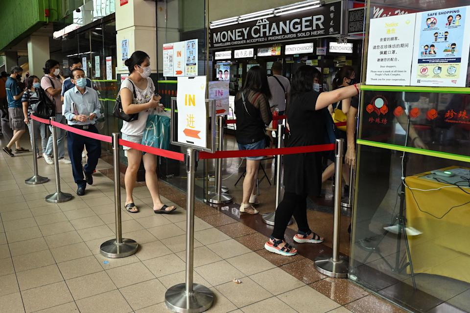 People queue as they wait to use a check-in service to enter a shopping centre in Chinatown in Singapore.