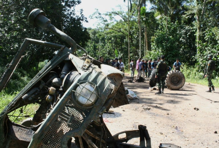 Thai security forces inspect the site of a roadside bomb attack in Thailand's southern Yala province in 2013