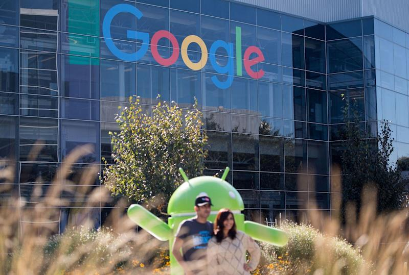 People pose for a picture near a Google sign and Android statue at the Googleplex in Menlo Park, California: JOSH EDELSON/AFP via Getty Images