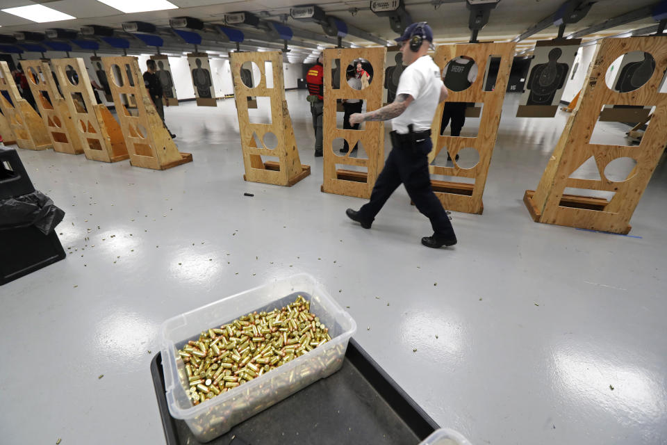 FILE - In this July 16, 2019, file photo, an officer taking part in training walks near a box of ammunition at the Washington State Criminal Justice Training Commission in Burien, Wash. The COVID-19 pandemic coupled with record sales of firearms have created a shortage of ammunition in the United States that has impacting competition and recreational shooters, hunters, people seeking personal protection and law enforcement agencies. (AP Photo/Ted S. Warren, File)