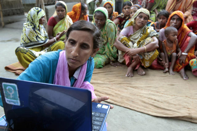 """In this Sept. 30, 2012 photo, Sathi Akhtar, a 29-year-old Bangladeshi woman known as Tattahakallayani or Info Lady shows a 15-minute video played in a laptop at one of their usual weekly meetings at Saghata, a remote impoverished farming village in Gaibandha district, 120 miles (192 kilometers) north of capital Dhaka, Bangladesh. Dozens of """"Info Ladies"""" bike into remote Bangladeshi villages with laptops and Internet connections, helping tens of thousands of people - especially women - get everything from government services to chats with distant loved ones. (AP Photo/A.M. Ahad)"""