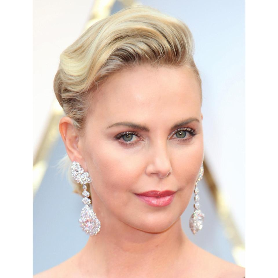 """Having shorter hair doesn't mean you can't play with volume. Look to Charlize Theron with her temple-length strands swooped up and over in soft waves. """"The cut and graduation is what makes this style work well for short hair,"""" says New York City-based hairstylist <a href=""""https://www.instagram.com/weddinghairnyc/"""" rel=""""nofollow noopener"""" target=""""_blank"""" data-ylk=""""slk:Sean Gallagher"""" class=""""link rapid-noclick-resp"""">Sean Gallagher</a>. Plus, the soft waves and height keep it from looking too severe. As far as your outfit, Gallagher suggests """"a modern silhouette — avoid anything with hard angles."""""""