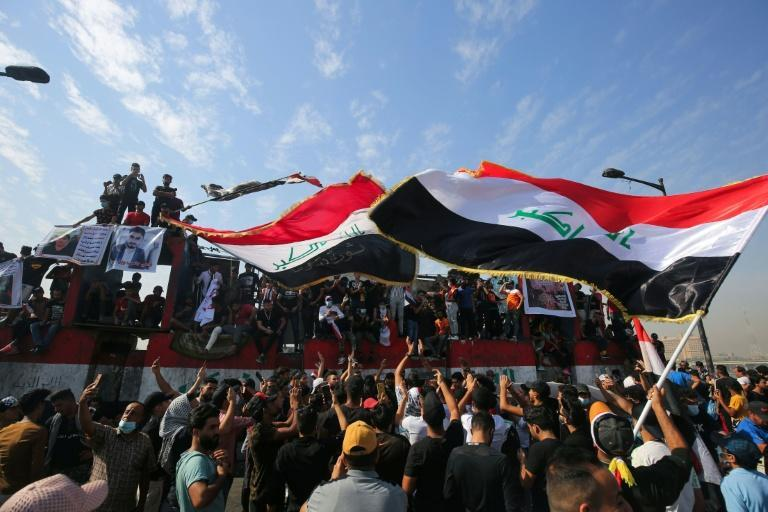 Iraqi demonstrators wave flags as they gather in Tahrir Square in the centre of the capital Baghdad