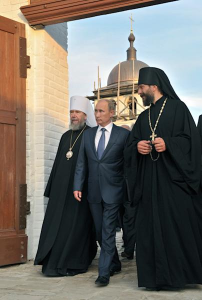 Russian President Vladimir Putin, center, flanked by Orthodox priests during a visit to an historical and architectural museum in Bolgar, about 700 kilometers (450 miles) east of Moscow, central Russia, Tuesday, Aug. 28, 2012. (AP Photo/RIA-Novosti, Alexei Nikolsky, Presidential Press Service)