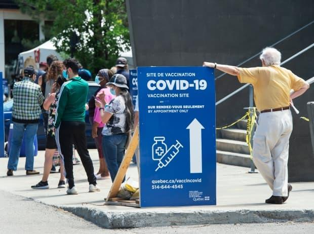 People line up to get their COVID-19 vaccine at a vaccination centre, Thursday, June 10, 2021 in Montreal. As of Thursday, the provincial vaccination rate stood at 76 per cent, and there were 251 patients in hospital.