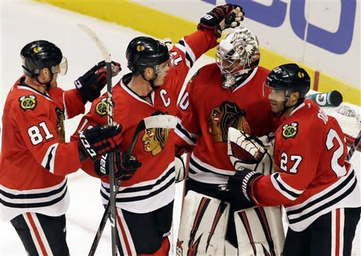 Chicago Blackhawks goalie Ray Emery, second from right, celebrates with Jonathan Toews (19), Marian Hossa (81) and Johnny Oduya (27) after the Blackhawks defeated the San Jose Sharks 2-1 during an NHL hockey game in Chicago, Friday, Feb. 22, 2013. (AP Photo/Nam Y. Huh)