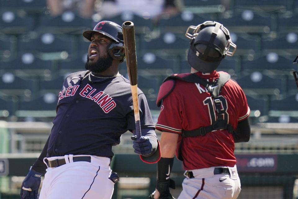 Cleveland Indians designated hitter Franmil Reyes, left, shouts after fouling off a pitch as Arizona Diamondbacks catcher Carson Kelly, right, looks for the ball during the second inning of a spring training baseball game Wednesday, March 3, 2021, in Goodyear, Ariz. (AP Photo/Ross D. Franklin)