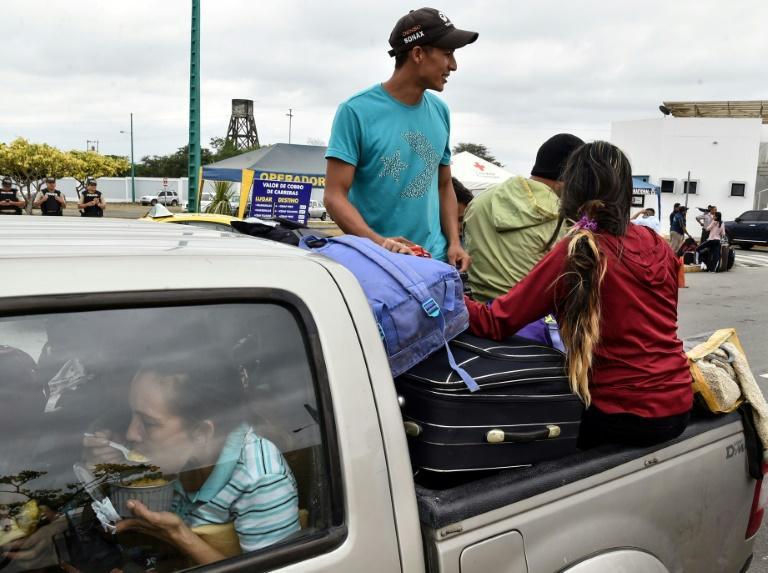 "Venezuelan migrants ride on the back of a pickup truck as they leave the binational border attention centre (CEBAF) in Huaquillas, Southern Ecuador in the border with Peru on August 24, 2018. Ecuador opened a ""humanitarian corridor"" to allow masses of migrants escaping Venezuela's free-falling economy to stream towards the Peruvian border Friday, hours before Lima puts new restrictions on entry into effect"