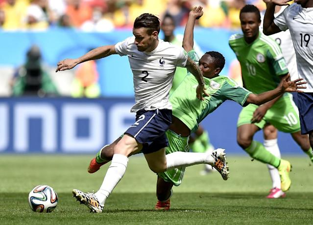 France's Mathieu Debuchy (2) is challenged by Nigeria's Ahmed Musa during the World Cup round of 16 soccer match between France and Nigeria at the Estadio Nacional in Brasilia, Brazil, Monday, June 30, 2014. (AP Photo/Martin Meissner)