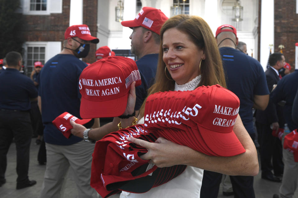Hats are passed out before President Donald Trump speaks to the City of New York Police Benevolent Association at an event at the Trump National Golf Club in Bedminster, N.J., Friday, Aug. 14, 2020. (AP Photo/Susan Walsh)