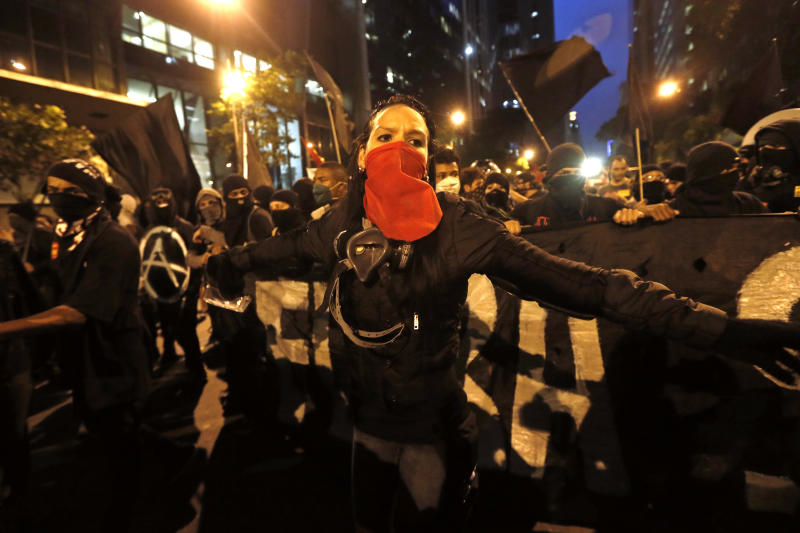 FILE - In this Oct. 15, 2013, file photo, masked members of the Black Bloc anarchist group join in a march in support of striking teachers in Rio de Janeiro, Brazil. The Black Bloc, a violent form of protest and vandalism that emerged in the 1980s in West Germany, has become a driving force in Brazil behind protests in recent weeks. The young Brazilians are following the main anti-capitalist tenets of earlier versions, smashing scores of banks and multinational businesses during demonstrations and directly confronting riot police.(AP Photo/Silvia Izquierdo, File)