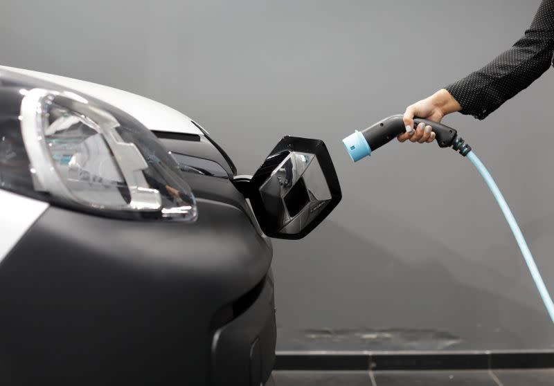 A woman holds a cable to charge up a Renault Kangoo ZE electric utility vehicle at a Renault automobile dealership in Cagnes-Sur-Mer