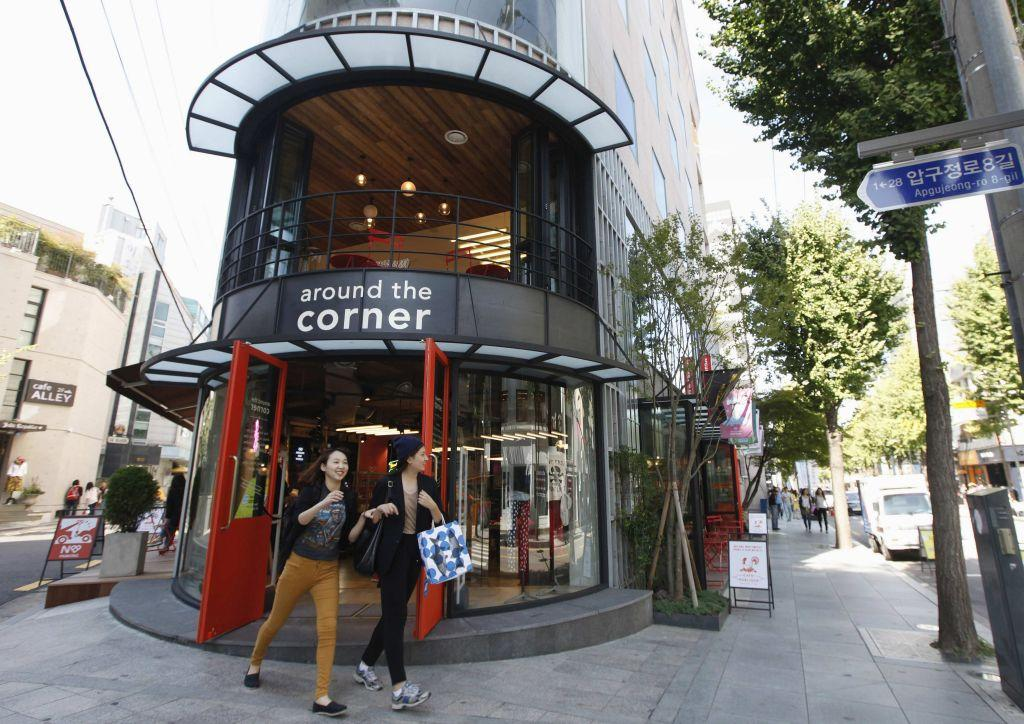 Women smile as they walk out of a shop on the Garosugil or the Tree-Lined Street in the Gangnam area of Seoul.