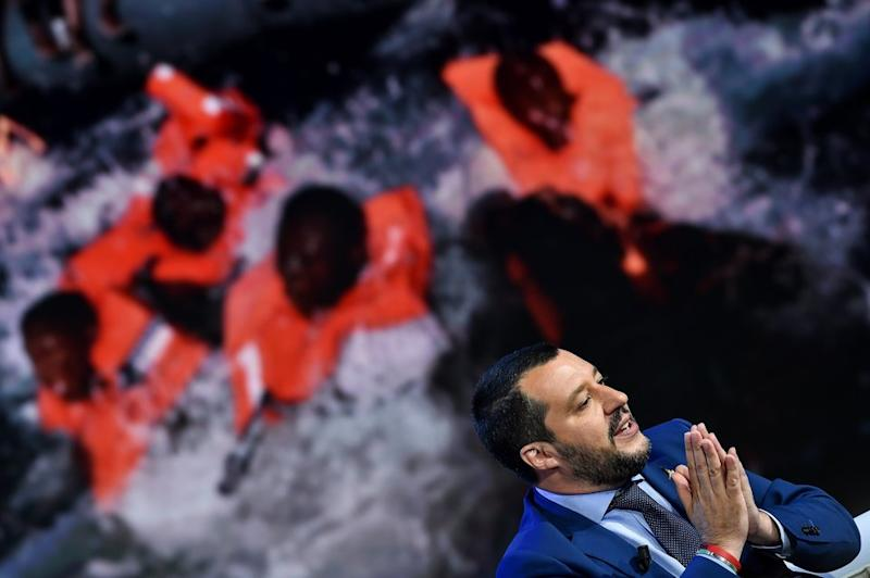 Italy's Interior Minister and Deputy Prime Minister Matteo Salvini speaks on an talian talk show as picture of migrants isdisplayedin the background.