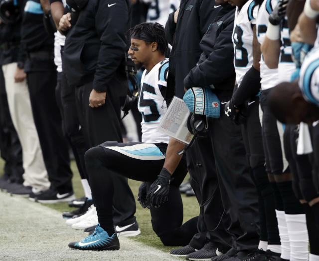 FILE - In this Sunday, Oct. 21, 2018, file photo, Carolina Panthers strong safety Eric Reid, center, takes a knee during the playing of the national anthem before an NFL football game against the Philadelphia Eagles in Philadelphia. Reid's grievance against the Cincinnati Bengals has been denied by an arbitrator, a decision that has irked the NFL Players Association. The grievance claimed that Reid wasn't signed by any team because of his anthem protests. Reid joined this Panthers this month. (AP Photo/Matt Rourke)