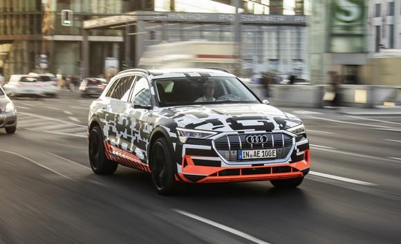 The Audi e-tron quattro prototype, an electric SUV wrapped in black and white camouflage, on a public road in Berlin, Germany.