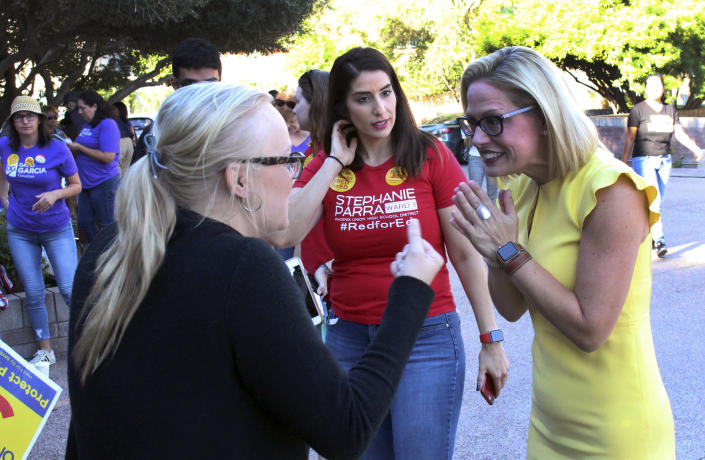 FILE--In this Nov. 3, 2018, file photo, a supporter, left, crosses her fingers as she talks with Democratic U.S. Senate candidate Kyrsten Sinema, right, at a get-out-the-vote event at the Arizona Education Association headquarters in Phoenix. The congresswomen running for Arizona Senate are in their final campaign swing as Republican Rep. Martha McSally barnstormed across rural Arizona and Sinema dashed around metro Phoenix. The two candidates were trying to turn out every last voter in the neck-and-neck race. (AP Photo/Bob Christie, File)