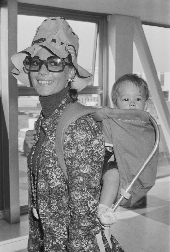 <p>The actress walks through an airport with her daughter, Natasha, strapped to her in a carrier. Natalie welcomed her firstborn with her second husband, Richard Gregson, in 1970. </p>
