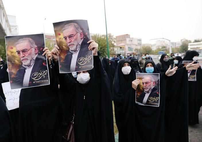 Image: Protesters hold the pictures of Iran's top nuclear scientist during a demonstration against his killing in Tehran on Saturday. (Majid Asgaripour/WANA / Reuters)