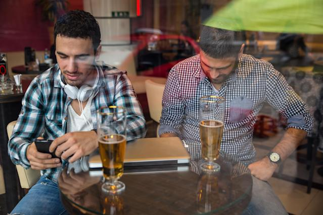 Two male friends sitting at the cafe and using smartphone. Addicted to social networking.Image taken from outside trough glass.