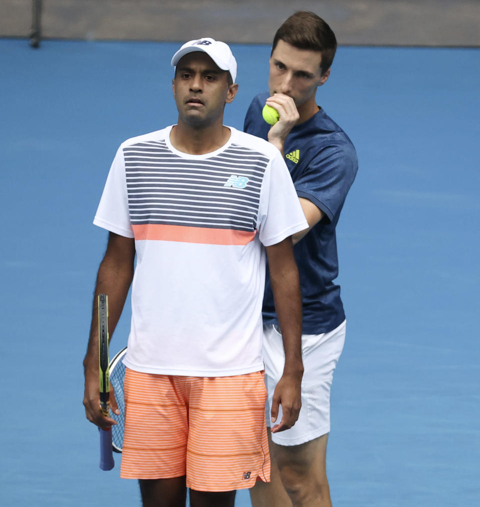Rajeev Ram, left, of the US and Britain's Joe Salisbury chat during their match against Croatia's Ivan Dodig and Slovakia's Filip Polasek in the men's doubles final at the Australian Open tennis championship in Melbourne, Australia, Sunday, Feb. 21, 2021.(AP Photo/Hamish Blair)