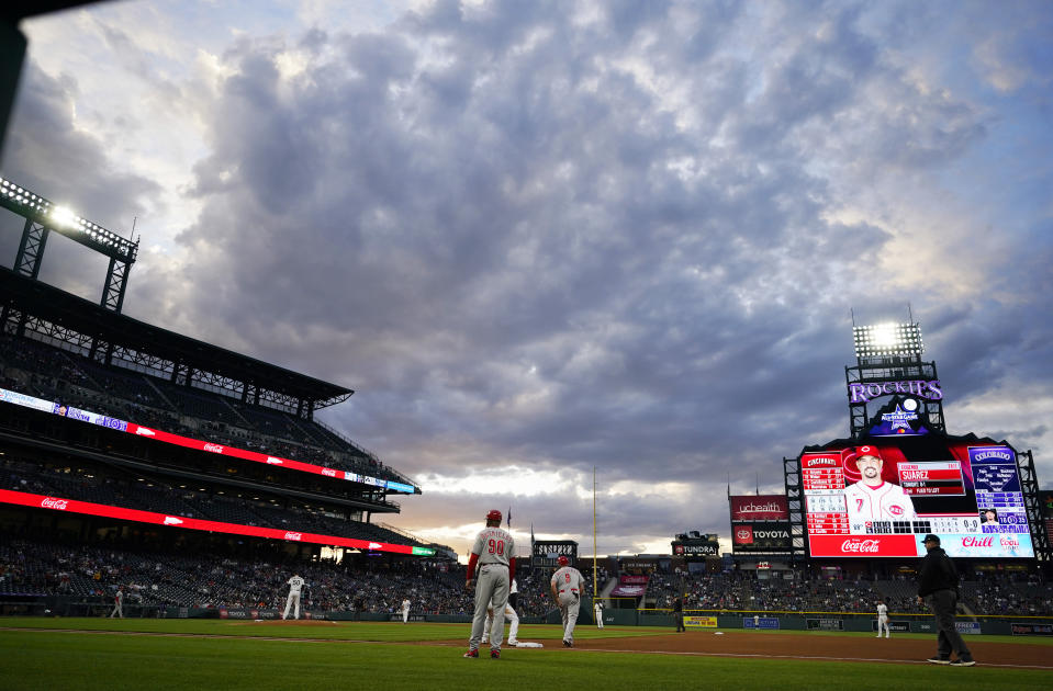 Clouds hang over Coors Field as Cincinnati Reds' Mike Moustakas leads off first base during the fourth inning of the team's baseball game against the Colorado Rockies on Thursday, May 13, 2021, in Denver. (AP Photo/David Zalubowski)