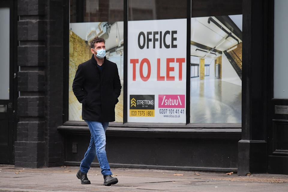 A pedestrian wearing a face mask as a precaution against the transmission of the novel coronavirus walks past a boarded up office space which is to let in east London on October 13, 2020. - Britain's unemployment rate has jumped to 4.5 percent as the coronavirus pandemic continues to destroy jobs, official data showed on October 13. (Photo by JUSTIN TALLIS / AFP) (Photo by JUSTIN TALLIS/AFP via Getty Images)