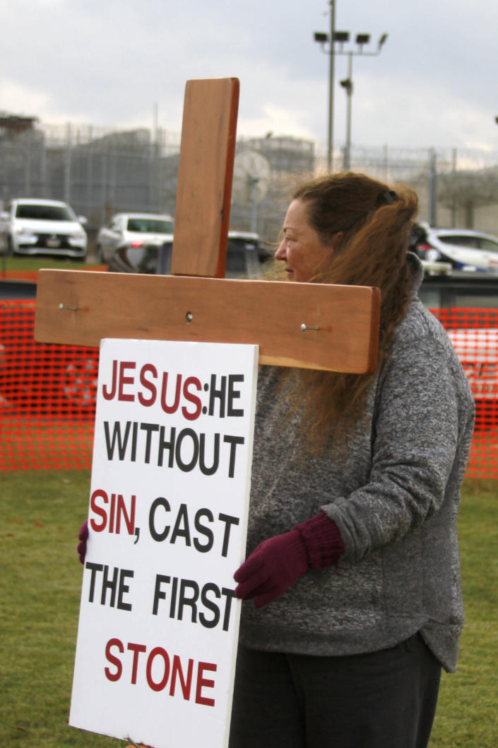 A protester holds a cross and sign during an anti-death penalty protest outside the South Dakota State Penitentiary in Sioux Falls, Monday, Nov. 3, 2019, where Charles Russell Rhines is scheduled to die Monday, by lethal injection for the death of a former co-worker. Officials are waiting to hear from the United States Supreme Court on three appeals filed by Rhines. The state attorney general's office said it will not proceed with the execution until the Supreme Court rules on the matter. (AP Photo/Stephen Groves)