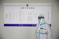 A security officer in a protective suit stands in front of a chart at the visitors' hall at the Urumqi No. 3 Detention Center in Dabancheng in western China's Xinjiang Uyghur Autonomous Region on April 23, 2021. Urumqi No. 3, China's largest detention center, is twice the size of Vatican City and has room for at least 10,000 inmates. (AP Photo/Mark Schiefelbein)