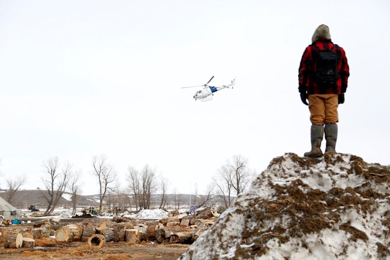A protester watches a law enforcement helicopter circle the main opposition camp against the Dakota Access oil pipeline near Cannon Ball, North Dakota, in February 2017. (Photo: Terray Sylvester / Reuters)