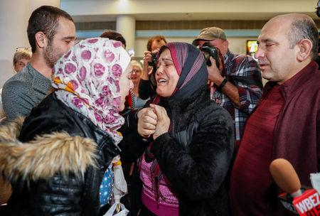 Syrian refugee Baraa Haj Khalaf reacts as her mother Fattoum cries and her father Khaled looks on after arriving at O'Hare International Airport in Chicago