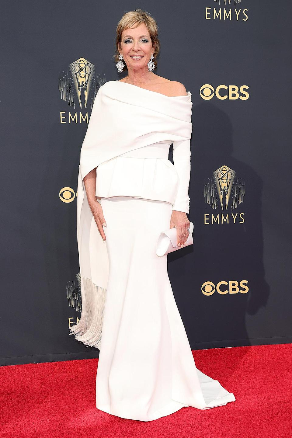 <p>in an Azzi & Osta belted peplum suit jacket, full length skirt and embellished shawl with tassels at the hem, plus statement earrings and white clutch.</p>