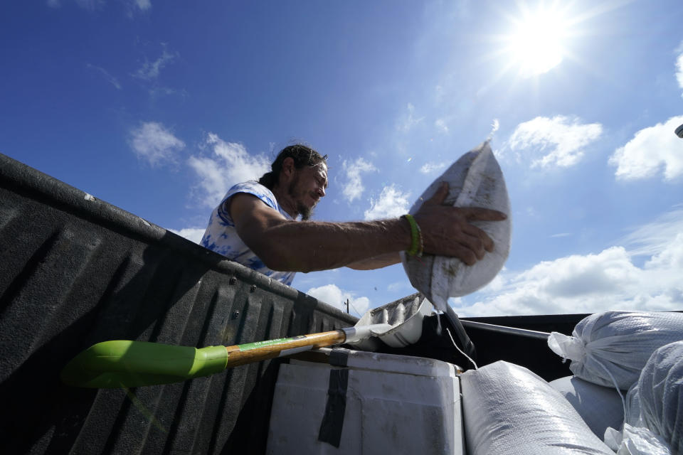 fill sandbags to protect their home in anticipation of Hurricane Delta, expected to arrive along the Gulf Coast later this week, in Houma, La., Wednesday, Oct. 7, 2020. (AP Photo/Gerald Herbert)