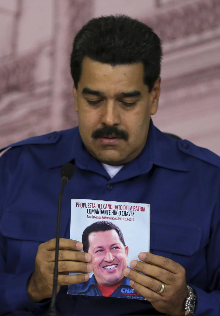 """Venezuela's President Nicolas Maduro holds a book emblazoned with an image of the late Hugo Chavez during a news conference at Miraflores presidential palace in Caracas, Venezuela, Monday, Dec. 30, 2013. Maduro said Monday that annual inflation hit 56.2 percent. Earlier the Central Bank said inflation slowed in the last two months of the year after Maduro took action to slash prices of appliances. The Central Bank justified a nearly three-week delay in issuing its report because of """"exceptional and historic"""" measures taken by Maduro to fight price speculators trying to destabilize the country. (AP Photo/Fernando Llano)"""