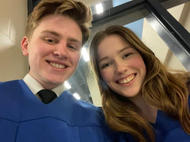 Grade 12 students Elijah Walsh, left, and his girlfriend Grace Brown in their graduation gowns at Lockview High School. (Elijah Walsh - image credit)